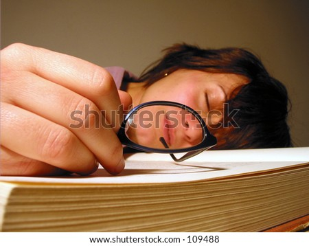 a girl with glasses sleeping after reading or studying a large boring law book