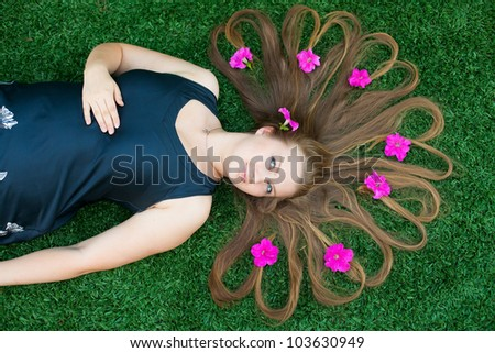 A girl with her hair lying on the lawn. In hair purple flowers. - stock photo