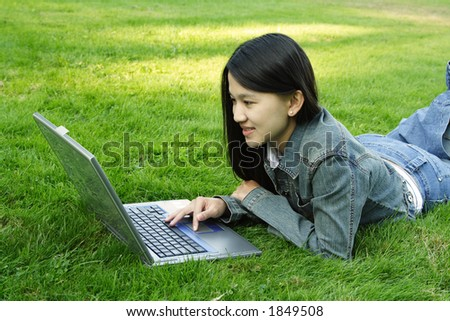 A girl with laptop at a park
