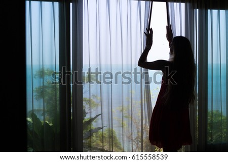 A Girl With Long Hair Standing Next To The Blind And Opening The Curtain  With Beautiful