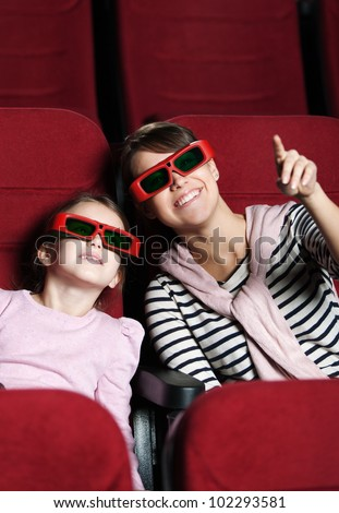 A girl with mother are watching 3D movie - stock photo