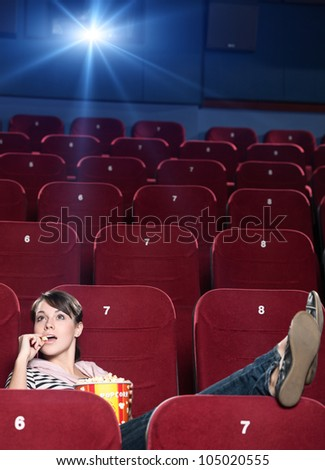 A girl with popcorn sitting alone at the cinema - stock photo