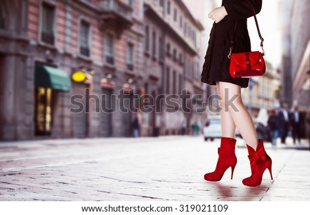 A girl with red bag and red boots in the street. Black coat.Beautiful legs in autumn winter time.  - stock photo