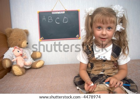 A girl with toys and school blackboard