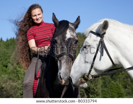 A girl with two horses in the woods in summer - stock photo