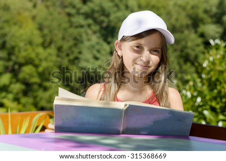 a girl with white hat, reads a book, outside - stock photo