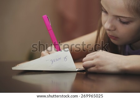 A girl writes a letter to the desire - stock photo