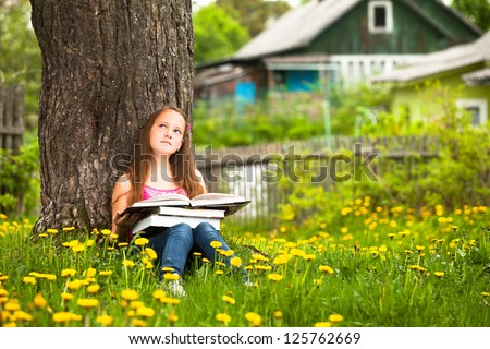 A girl, 11 years old, reads a book in the meadow. - stock photo