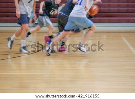 a girls basketball team running up or down the court with motion blur from a slow shutter speed (NOTHING IS IN FOCUS) toned with a retro vintage instagram filter effect app or action  - stock photo