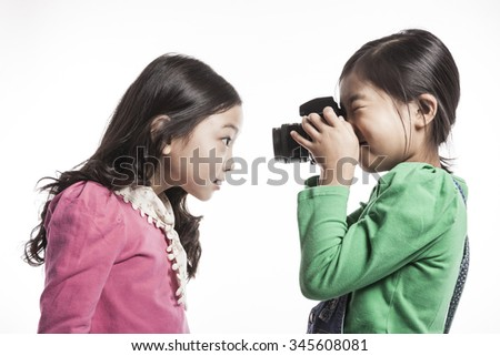 A girls(kid, student, woman, female) wearing pink and green shirts hold a camera with friend with smile isolated white. - stock photo