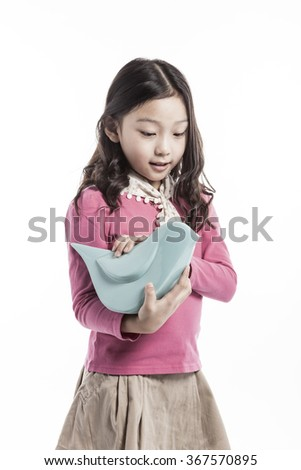 A girls(woman, female) wearing pink blouse and skirt hold a blue ceramic bird with smile(happy) isolated white at the studio.