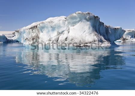 A glacial iceberg and its reflection floating on the Iceberg Lagoon, Jokulsarlon, Iceland - stock photo