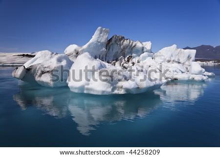 A glacial iceberg and its symmetrical reflection floating on the Iceberg Lagoon, Jokulsarlon, Iceland - stock photo