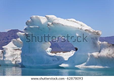 A glacial iceberg with a hole through its center floating on the Iceberg Lagoon, Jokulsarlon, Iceland - stock photo