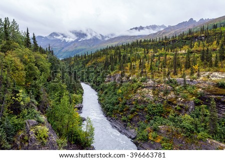 A glacial river cuts through the mountains along the Richardson Highway near Thompson's pass. - stock photo