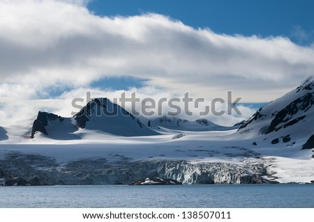 A glacier heading down from a mountain range into the ocean, Hornsund, Norway