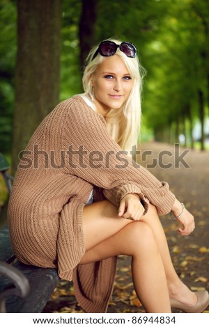 A glamorous young blonde fashion model sits on a park bench in a wool knee-length jersey and sunglasses. - stock photo