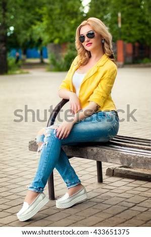 A glamorous young blonde fashion model sits on a park bench in yellow jacket wearing sunglasses - stock photo