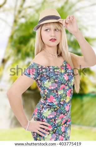 a glamorous young woman in short dress with summer hat - stock photo