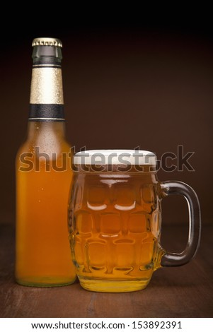 A glass and a bottle of beer on a wooden table.