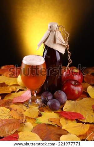 A glass and a bottle of beer standing over yellow leaves with an assortment of fruits over a dark warm background