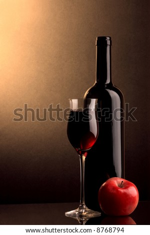 a glass and a bottle of red wine and an apple