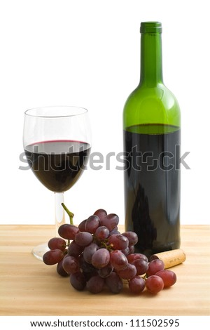 A glass and a bottle of red wine with grapes on a wooden table, isolated on a white bakground.