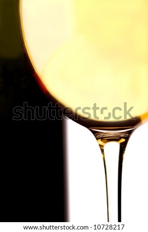 a glass and a bottle of white wine on a white background