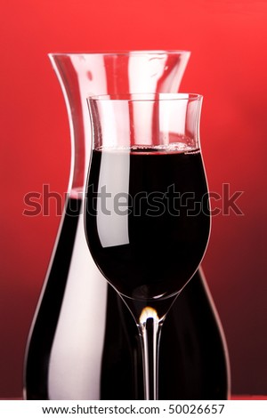 a glass and a jug of red wine