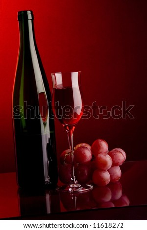 a glass and bottle and grape