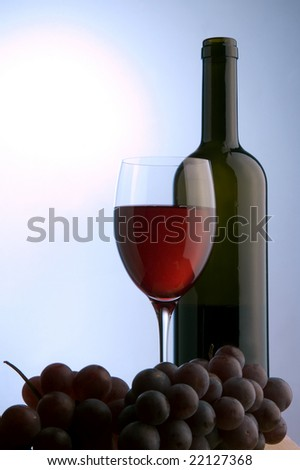 a glass and bottle of red wine and grape