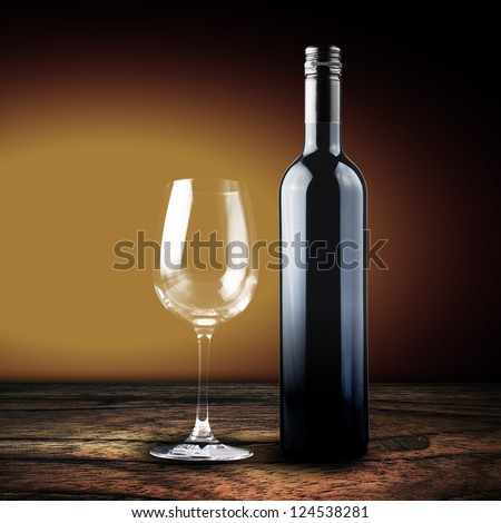 A glass and bottle of red wine on wood and yellow background