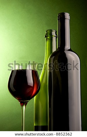 a glass and bottles with red wine