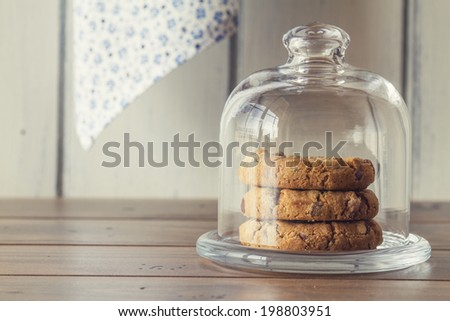 A glass bell jar with chocolate chip cookies on a wooden table with a white background. Vintage Style. - stock photo