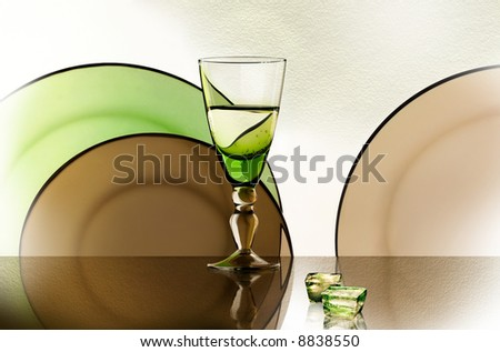 A glass beside a stack of white plates - on white background