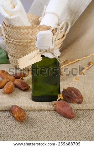 A glass bottle of dates seeds oil. Dates in the background. - stock photo