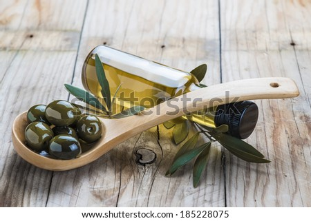 A glass bottle of olive oil and a wooden spoon with  olives on a table - stock photo