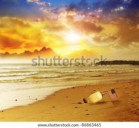 A glass bottle with a small American flag on a beautiful beach with vibrant sunset in background - stock photo
