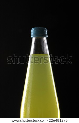 A glass bottle with yellow soft drink isolated black. - stock photo