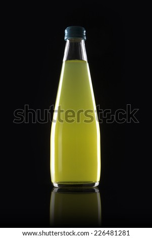 A glass bottle with yellow soft drink reflective bottom isolated black. - stock photo
