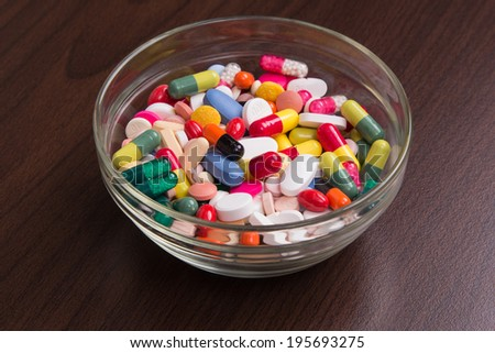 A glass bowl filled with drugs on table - stock photo