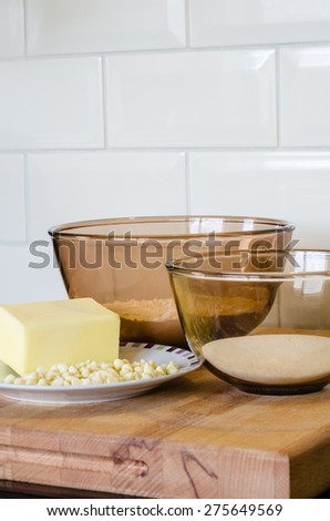 A glass bowl of flour next to a glass bowl of sugar behind a bar of butter on a white plate with white chocolate chips. All baking ingredients on top of a wood surface. Vertical. - stock photo