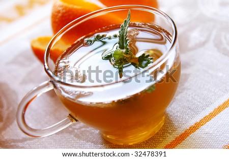 A glass cap of cold orange-mint tea with ice, closeup - stock photo