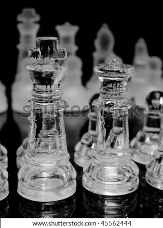 A glass chess set arranged in play, focusing on the king and queen - stock photo