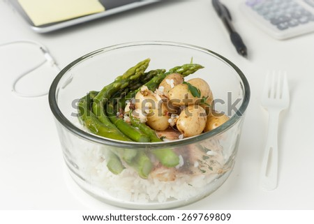 a glass container with lunch with leftovers on a desk at work - stock photo
