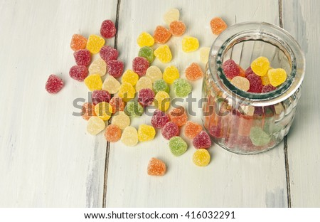 A glass container with vibrant gum drops, with more candies on a light wooden texture beside it, with copyspace - stock photo