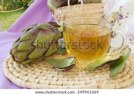 A glass cup of artichoke herbal tea on a woven surface. Artichoke in the background - stock photo
