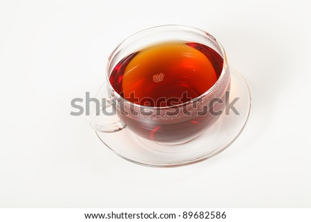 A glass cup of hot tea on a saucer. Focus on the bubbles. - stock photo
