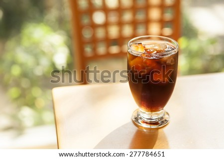 A glass cup of ice black coffee on the wood table with shadow of leaves at the early spring, summer.