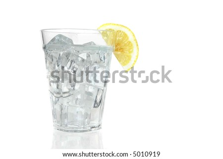 A glass filled with ice and sparkling water and a slice of lemon on a white background.
